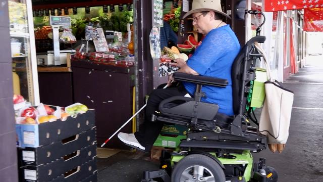 Woman in her electric wheelchair entering shop